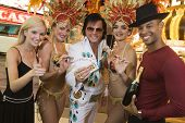 Elvis impersonator standing with casino dancers and a group of people