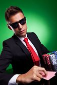 Business man with poker face playing at high stakes, on green background