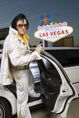 Elvis impersonator in front of a 'Welcome to Las Vegas' sign