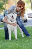 young happy woman playing with dog outdoors
