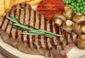 Sirloin beef steak with chips, peas, tomato and sauteed mushrooms.