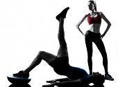 personal trainer man coach and woman exercising abdominals push ups on bosu silhouette  studio isola
