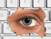 Woman's eye peering through hole in laptop