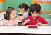 image of kindergarten  - Little boy using digital tablet with female friend at desk in kindergarten - JPG