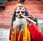 KATHMANDU,NEPAL-MAY 18: Sadhu play flute at Pashupatinath Temple in Kathmandu, Nepal on May 18, 2013. The two primary sectarian divisions in sadhu community are Shaiva sadhus and Vaishnava sadhus.