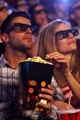 Young couple eating popcorn in multiplex movie theater, watching 3D movie. Focus on popcorn.