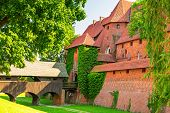 foto of fortified wall  - The wall and towers of Malbork castle in summer scenery - JPG