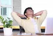 Relaxed young Asian businessman in office - break time