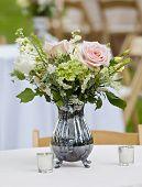 flower arrangement in old silver pitcher
