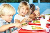 stock photo of playground school  - Elementary Pupils Enjoying Healthy Lunch In Cafeteria - JPG