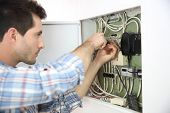 Electrician fixing cable in domestic electrical box