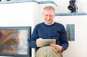 Quality of life - Older man or Pensioner sitting at home in front of the furnace, writing emails on