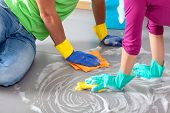 stock photo of suds  - Happy couple cleaning floor together in free day - JPG
