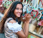 Young woman in Dirndl costume together with German Gingerbread heart
