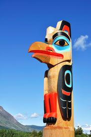 stock photo of tlingit  - Eagle Totem Pole Against a Blue Sky located in Carcross Yukon Canada Copy Space Vertical - JPG