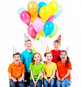Happy boys and girls in party hat with colored balloons sitting on the floor - isolated on white.
