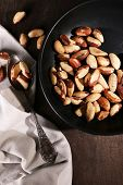 Tasty brasil nuts in pan on wooden background