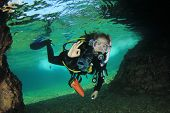 stock photo of cave woman  - Young Woman Scuba diving into underwater cave - JPG