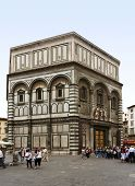Florence, Italy - May 15, 2009: The baptistery opposite Florence Cathedral, tourists in front.