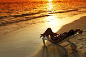 Woman in chaise-lounge relaxing on sunset beach