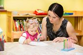 stock photo of montessori school  - Mother and child girl playing in kindergarten in Montessori preschool Class - JPG