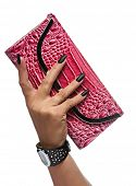 closeup of the woman's hand with black nail art manicure holding a red crocodile skin texture clutch on white studio background