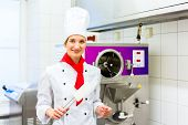 Female Chef preparing ice cream with machine in gastronomy parlor kitchen