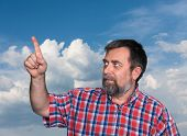 Middle-aged Men Pointing His Forefinger Towards A Blue Sky