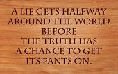 A lie gets halfway around the world before the truth has a chance to get its pants on - quote on wooden red oak background