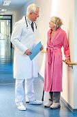 image of hospital gown  - Doctor talking to an elderly woman patient dressed in a pink dressing gown and holding a walking stick in the corridor of the hospital with a file in his hands - JPG