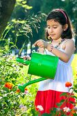 Young Girl Using Watering Can Outdoors