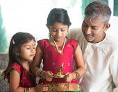 Indian family in traditional sari celebrate diwali or deepavali at home. Little girl hands holding o