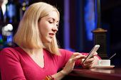 picture of handphone  - Young attractive lady at bar talking on phone - JPG