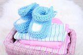 Baby clothes in basket on floor in room