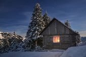 stock photo of roof-light  - wooden house in winter forest - JPG