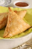 stock photo of samosa  - Samosas a spicy blend of vegetables or meat wrapped in a deep fried triangular pastry parcel - JPG