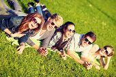 summer holidays, education and teenage lifestyle concept - group of students or teenagers lying on grass in park