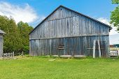 Old Wooden Barn Against A Blue Sky.