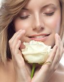 closeup portrait of attractive  caucasian smiling woman blond isolated on white studio shot lips face hair head and shoulders eyes closed flower white rose aroma