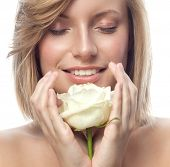 closeup portrait of attractive  caucasian smiling woman blond isolated on white studio shot lips toothy smile face hair head and shoulders  eyes closed hands white rose flower aroma