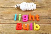 Light bulb word formed with colorful letters on wooden background