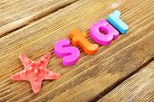 Star word formed with colorful letters on wooden background