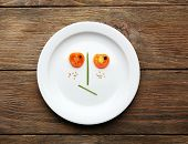 Vegetable face on plate on wooden table