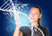Beautiful businesswoman in dress smiling and presses finger on model of DNA
