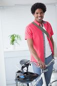 Happy businessman standing with his bike in his office