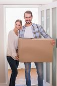 Cute couple carrying cardboard box in their new home