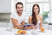 Young couple using tablet at breakfast at home in the kitchen