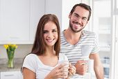 Young couple smiling at the camera having coffee at home in the kitchen