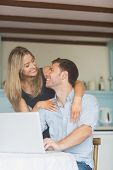 Cute couple using laptop together at home in the kitchen