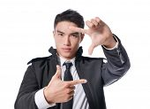 Young businessman with perfect white smile framing face with hands